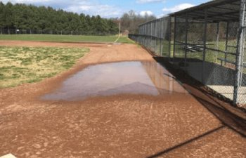 water ponded up on the school baseball field due to poor drainage